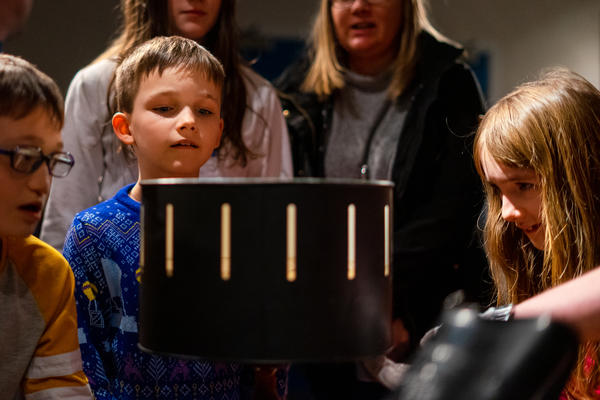 Visitors getting hands-on during a collections tour, exploring how a zoetrope produces the illusion of moving images. Photo credit: Nathan Buckley.